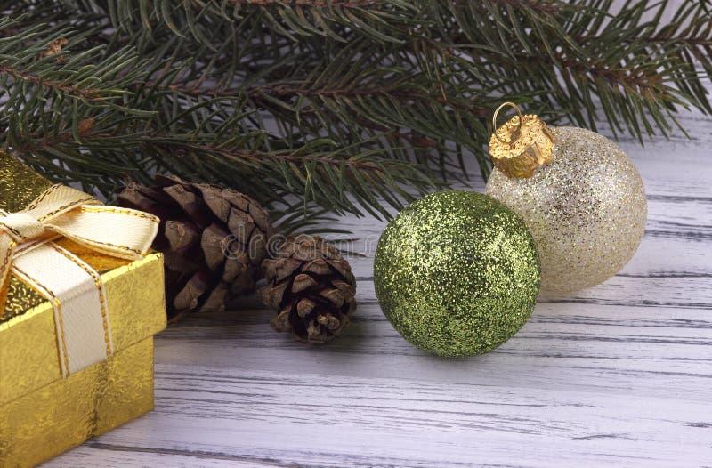 圣诞节Xmas新年与金黄礼物盒绿色和银色球自然冷杉的假日背景分支在白色木的锥体 库存图片
