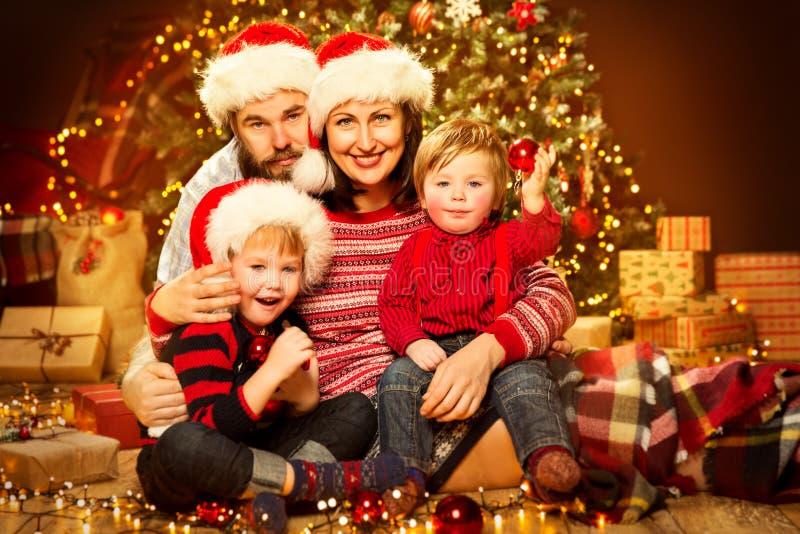 圣诞节Xmas树、愉快的父亲母亲孩子和婴孩家庭前面在红帽公司中 免版税库存图片