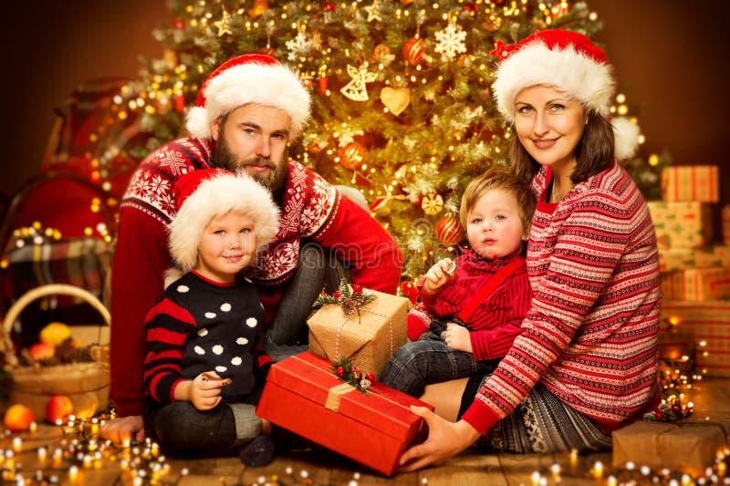 圣诞节Xmas树开放当前礼物盒、父亲母亲孩子和婴孩家庭前面红色帽子的 免版税库存照片