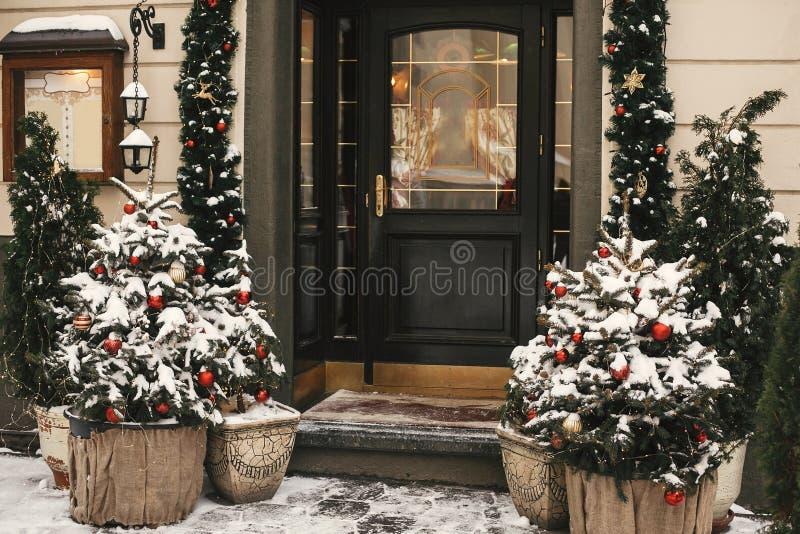 圣诞街装饰 商店门前的时尚圣诞树,上面有红色和金色的饰品和节日灯光,上面覆盖着雪 库存照片