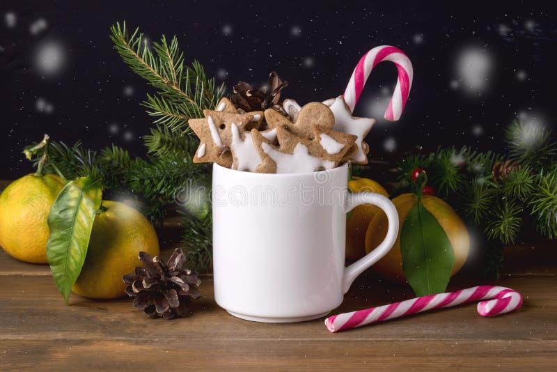 圣诞装饰用在白色杯圣诞节欢乐假日概念柑橘棒棒糖冷杉的姜饼曲奇饼分支Woode 免版税图库摄影