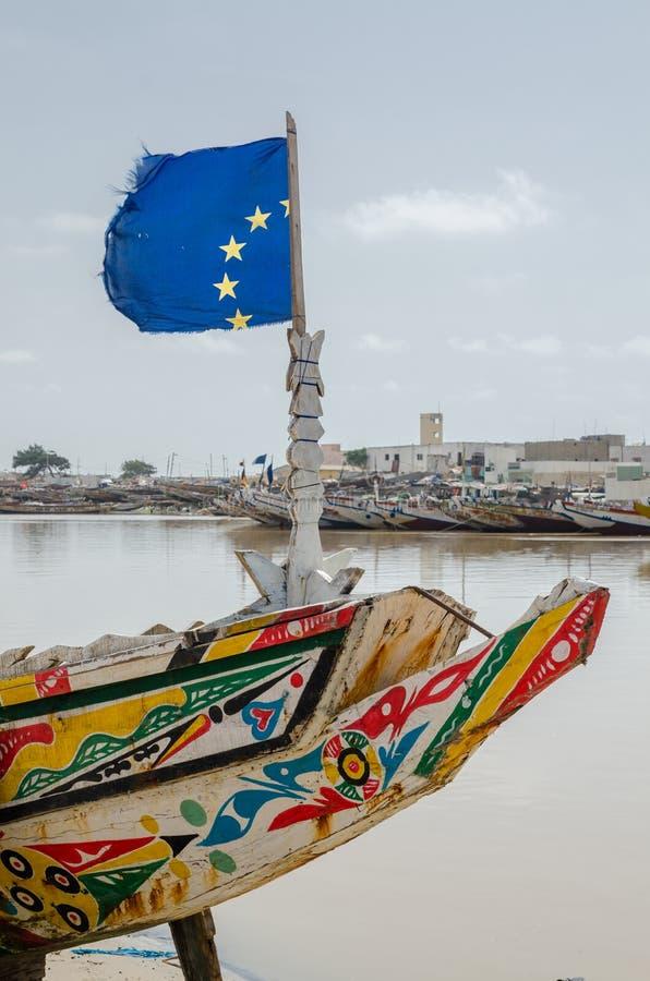 圣路易斯,塞内加尔- 2014年10月12日:五颜六色的被绘的木渔船或独木舟有欧盟旗子的在海岸 库存照片