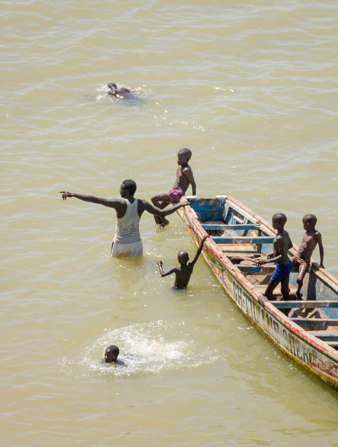 圣路易斯,塞内加尔- 2013年10月20日:未认出的非洲孩子和成年人游泳在木小船旁边 免版税库存照片