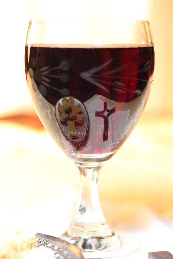 圣餐的基督徒标志-面包的十字架和片断在红葡萄酒玻璃酒杯被反映  免版税库存图片