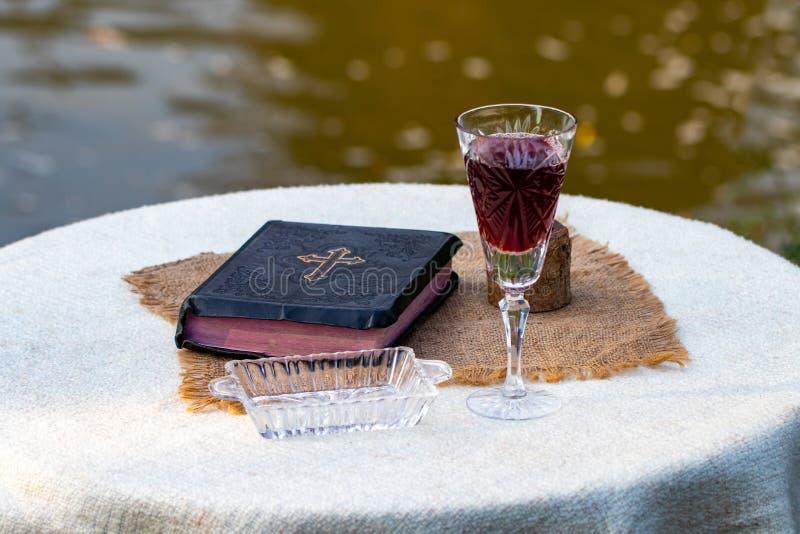 圣餐采取 杯玻璃用红葡萄酒、面包和圣洁围嘴 库存图片