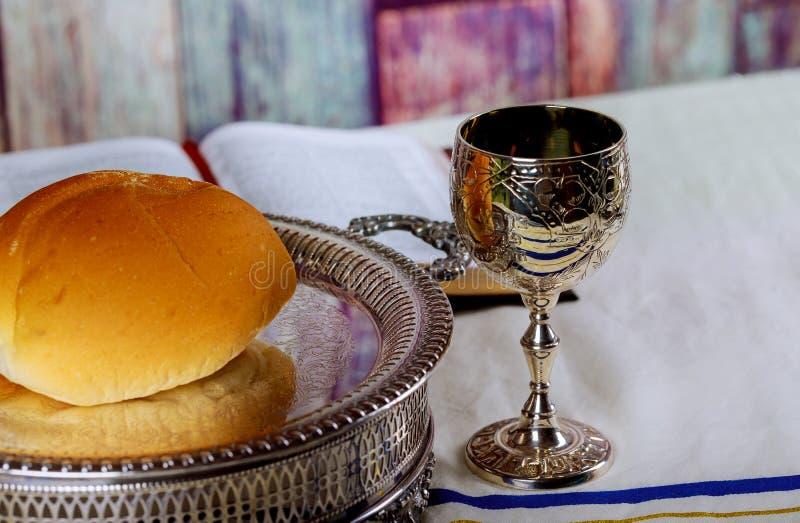 圣餐采取 杯玻璃用红葡萄酒、面包和圣经在木桌特写镜头 免版税库存照片