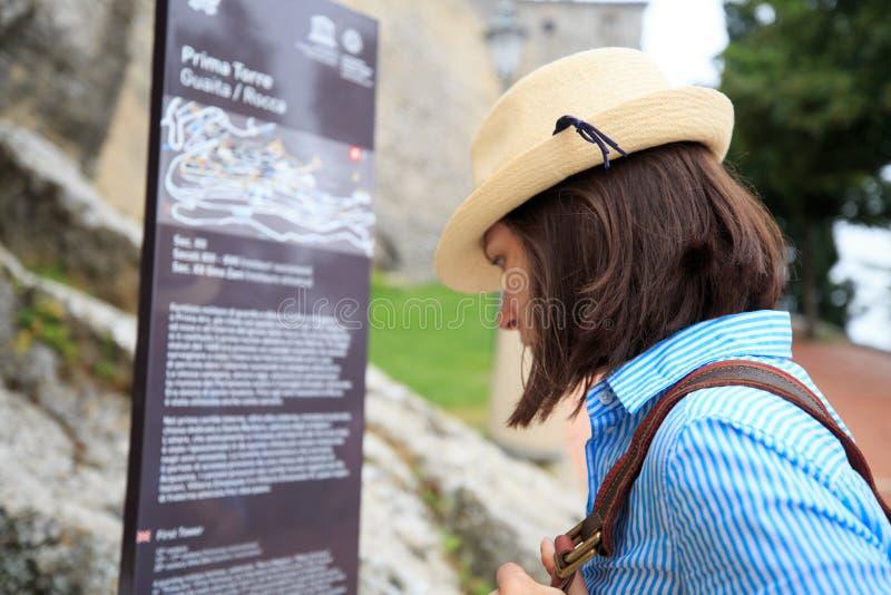 圣马力诺堡垒的旅游女孩读书信息 库存照片