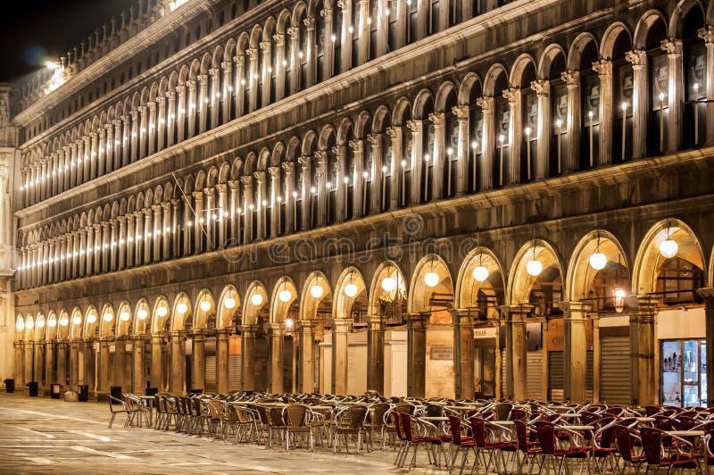 圣马可广场大厦在晚上照亮了,与桌并且主持威尼斯意大利 免版税库存图片