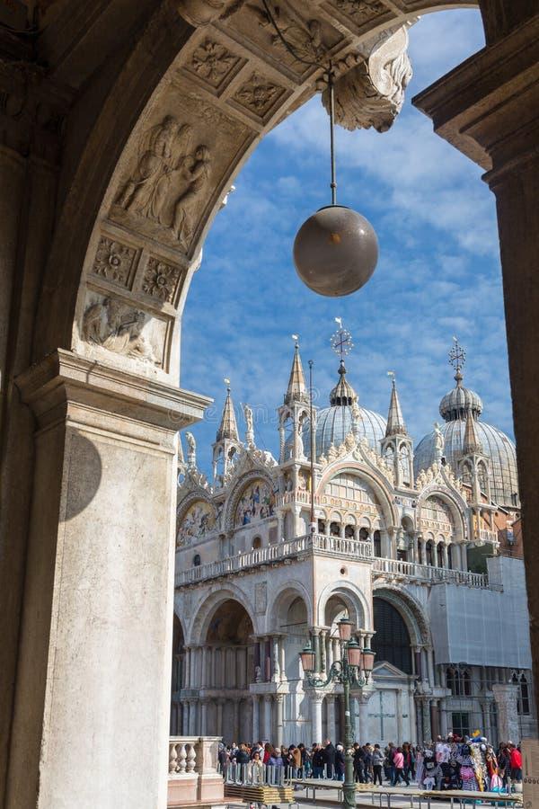 圣马尔谷教堂广场的游人晴朗的春日在威尼斯,意大利 大教堂二圣马尔谷教堂视图通过曲拱 库存照片