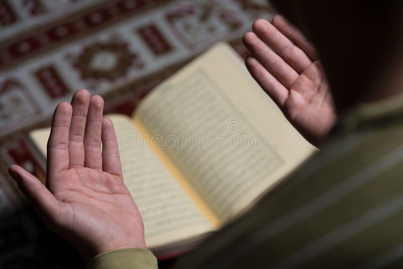 读圣洁伊斯兰教的书古兰经的阿拉伯回教人 免版税库存图片