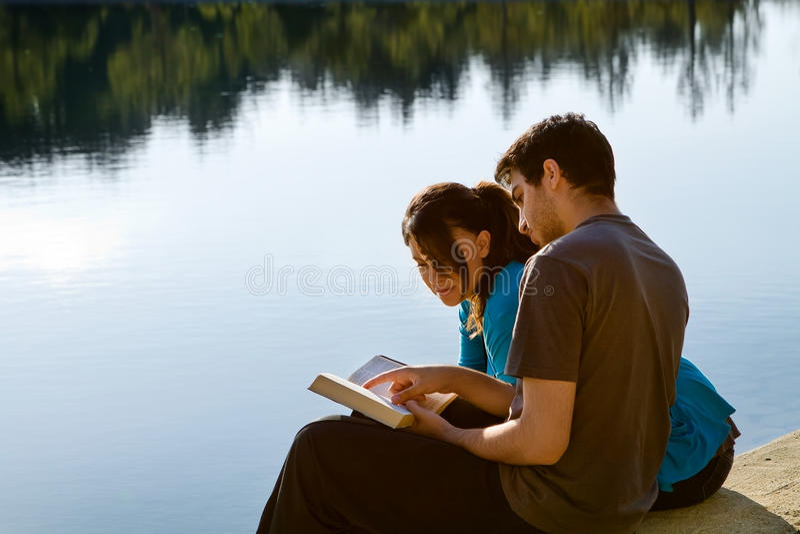 读圣经的夫妇由湖 免版税库存照片