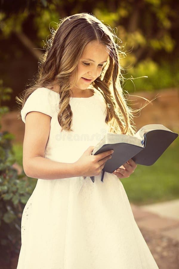 读圣经的逗人喜爱的小女孩 免版税库存照片
