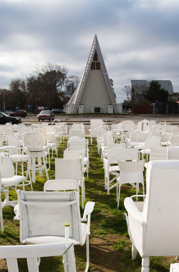 在'纸板大教堂,克赖斯特切奇前面的白色椅子 库存照片