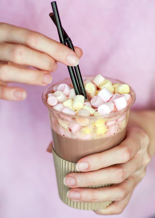 在一个一次性杯子的蛋白软糖可可粉有两支管的在手上 免版税图库摄影