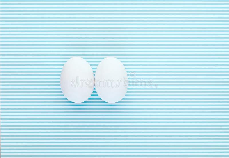 在一个五颜六色的白色和蓝色镶边背景的两个鸡蛋 免版税库存照片