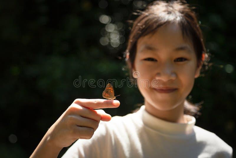 在一个亚裔女孩的手指的小的蝴蝶,逗人喜爱的女孩learni 库存图片