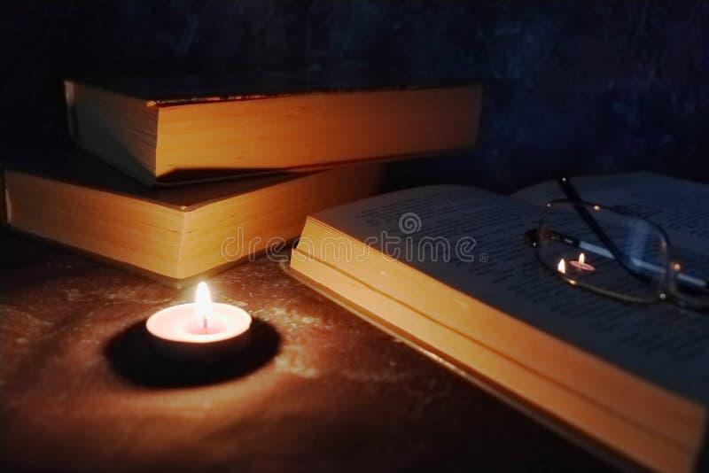 在一个亲密的设置的被点燃的蜡烛,旧书,时常被染黄,在一条被编织的黄色螺纹的玻璃 免版税库存照片