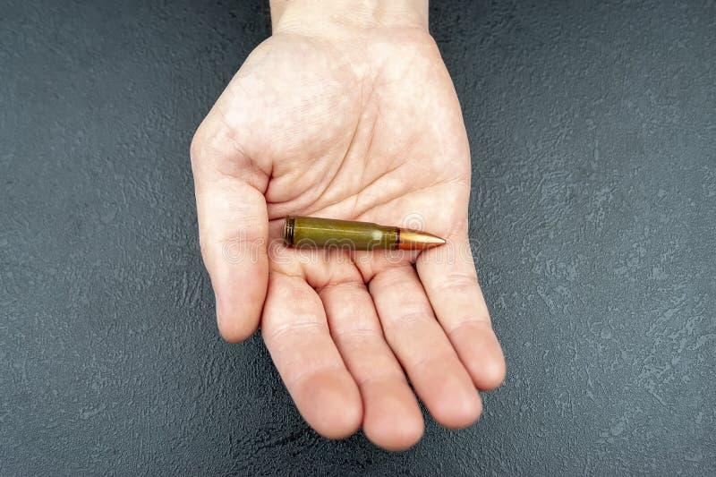 在一个人的手上的卡拉什尼科夫攻击步枪的一个绿色弹药筒 免版税库存照片