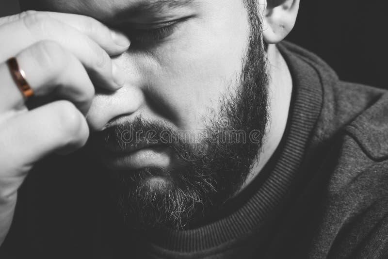 在一个人的手指的已婚圆环 拿着他的头的一个人的哀伤的画象 家庭问题、废弃物和暴力 免版税库存图片
