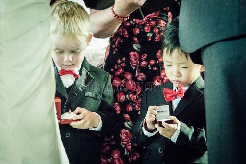 在一个传统婚礼期间,孩子打开结婚戒指箱子 库存照片