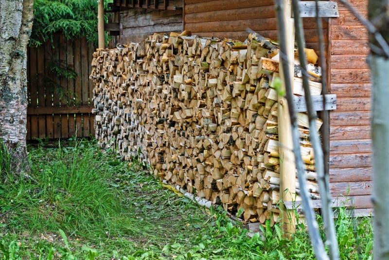 在一个传统木房子前面被存放的木柴 免版税库存照片
