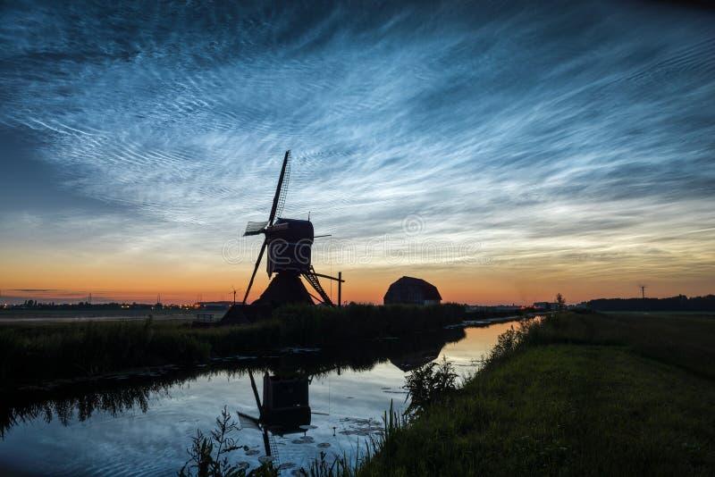 在一个传统荷兰风景的生物发光云彩与沿运河的风车 盛夏夜晚火仪式在二举行 库存图片