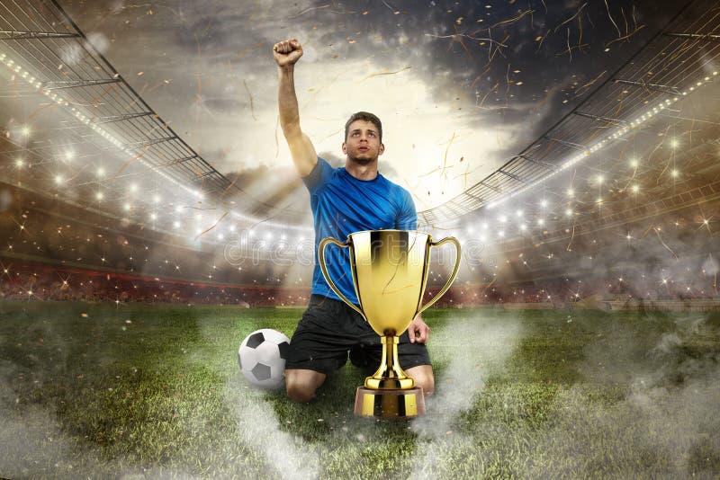 在一个体育场中间的金黄优胜者` s杯子有观众的 免版税库存照片