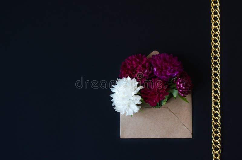 在一个信封的菊花花在黑背景 库存照片
