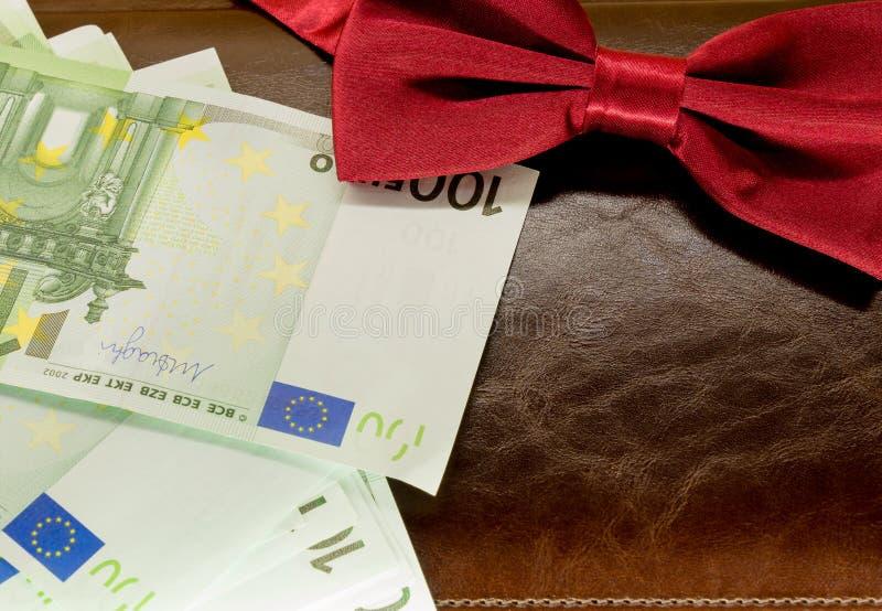 在一个信封的金钱在棕色笔记薄背景 免版税库存图片