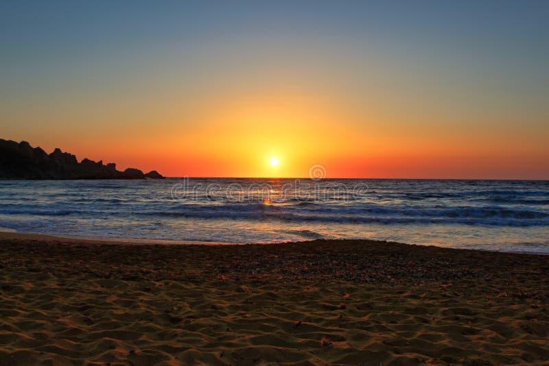 在一个偏僻的地中海沙滩的美好的日落 库存图片