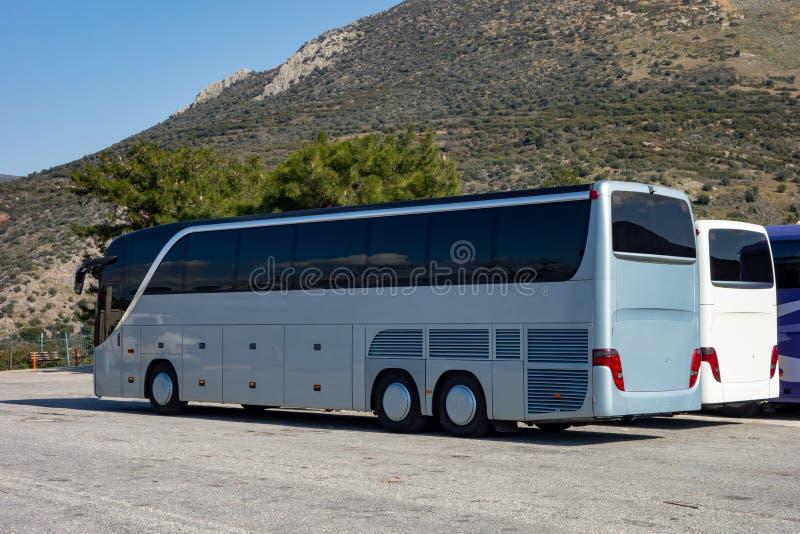 在一个停车场停放的公共汽车等在热的夏天天气游人 图库摄影