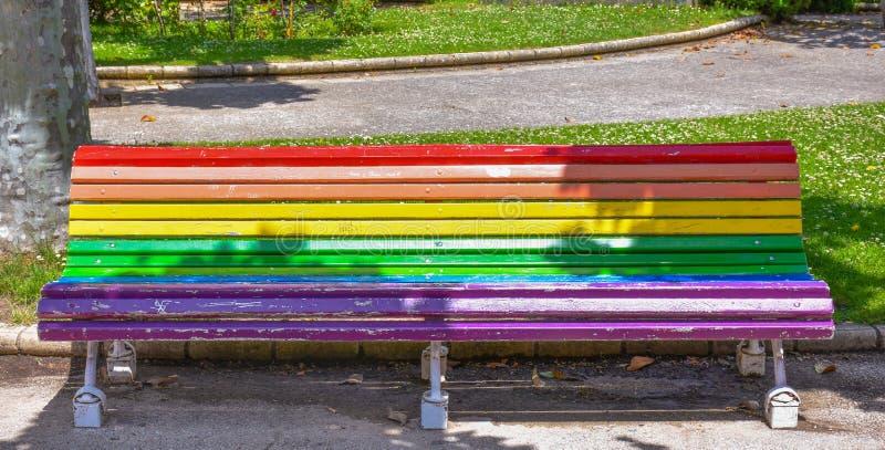 在一个公园的长凳绘与彩虹颜色 彩虹旗子或颜色是标志a同性恋者,两性和 图库摄影