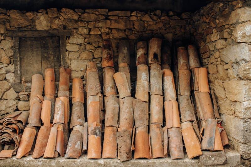 在一个农村房子的一个石墙安置的老瓦 库存图片