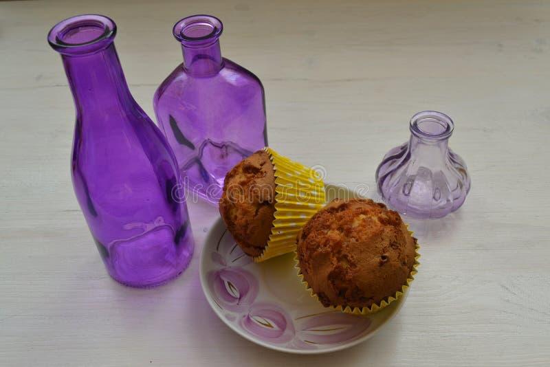 在一个冷菜盘的巧克力杯形蛋糕在与紫罗兰色decoratif元素的白色破旧的桌上 免版税库存照片