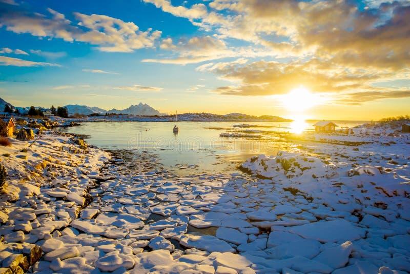 在一个冻湖的低潮期间与冰中小型的片断的惊人的日落视图忘记了 免版税库存图片