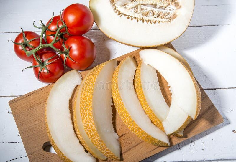 在一个分支和成熟瓜的蕃茄在一张木白色桌上 免版税图库摄影