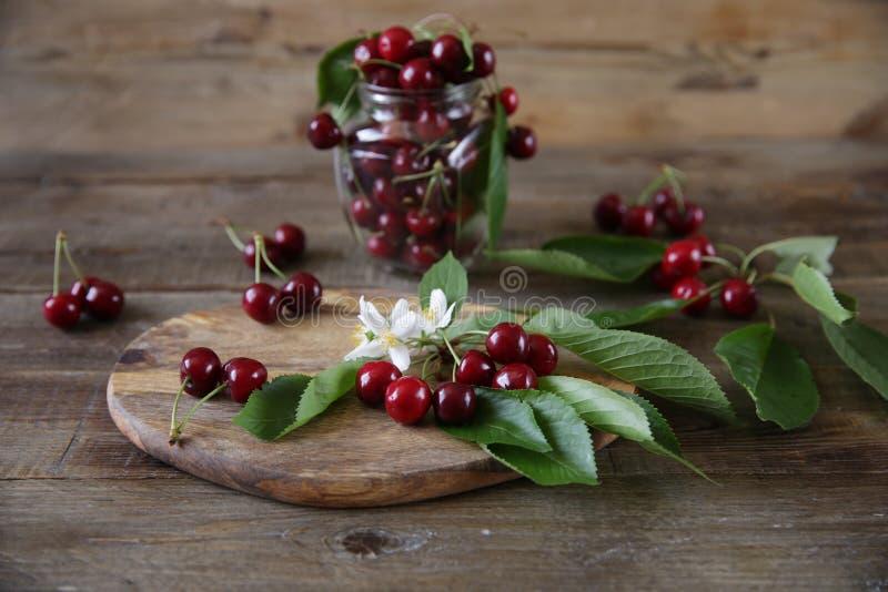 在一个分支的新鲜的有机樱桃与叶子和白花用一棵樱桃在一个玻璃瓶子在木土气背景 免版税库存照片