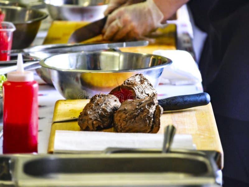 在一个切板的煮熟的烤牛肉 烹调主要类,有学会如何的人的车间在表附近烹调 免版税库存图片