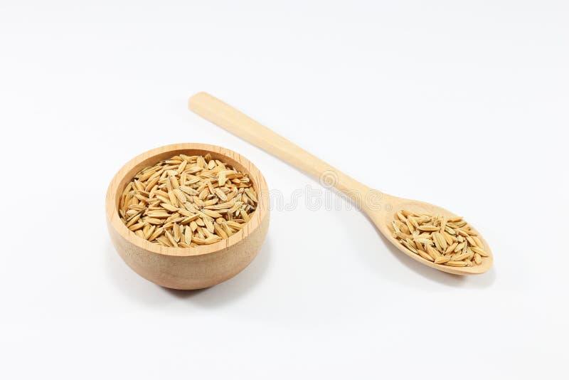在一个匙子和杯子的谷物在白色背景 库存照片