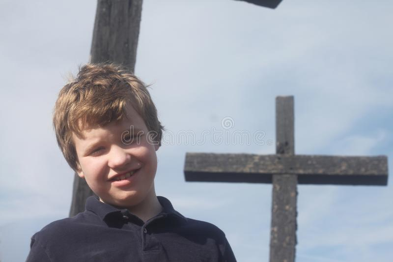 在十字架前面的微笑的自我中心男孩 库存照片