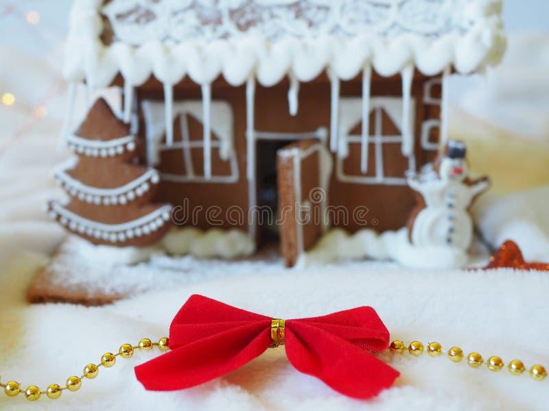 在一个华而不实的屋前面的圣诞节红色弓在背景中 库存图片