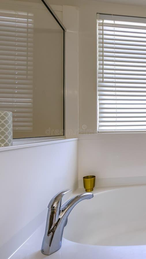在一个卫生间里面的垂直的闪烁的白色浴缸有在墙壁上的一个大镜子的 库存图片
