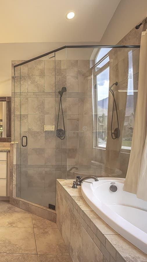 在一个卵形浴缸旁边的垂直的框架淋浴间在与帷幕的一个被成拱形的窗口前面 库存图片