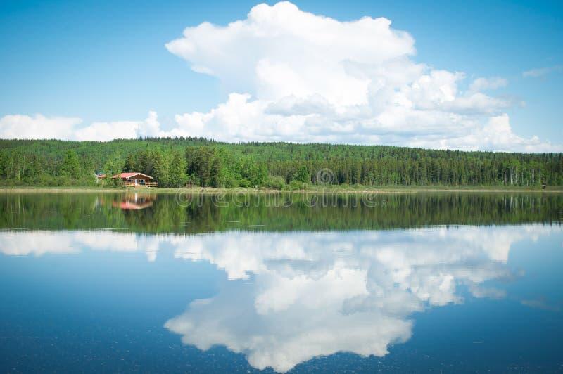 在一个反射性湖的被隔离的客舱在育空,加拿大 免版税库存照片