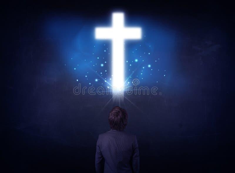 在一个发光的十字架前面的商人 库存照片