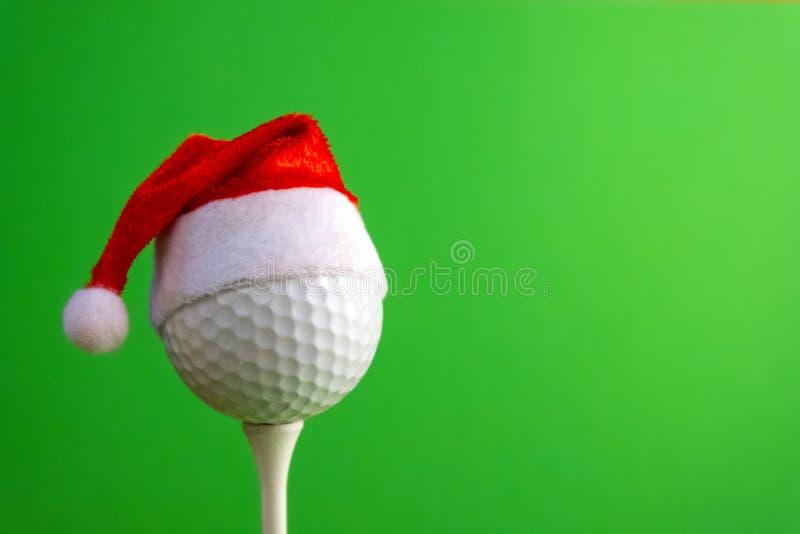 在一个发球区域的高尔夫球与一个红色圣诞老人项目帽子 设计贺卡的模板高尔夫球运动员的新年或圣诞节 绿色 库存图片