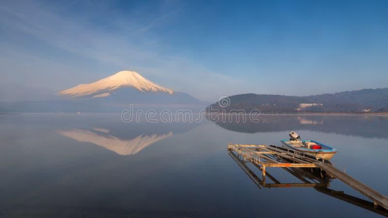 在一个口岸的一条小老小船与富士山的美好的水反射在Yamanaka湖的 库存照片