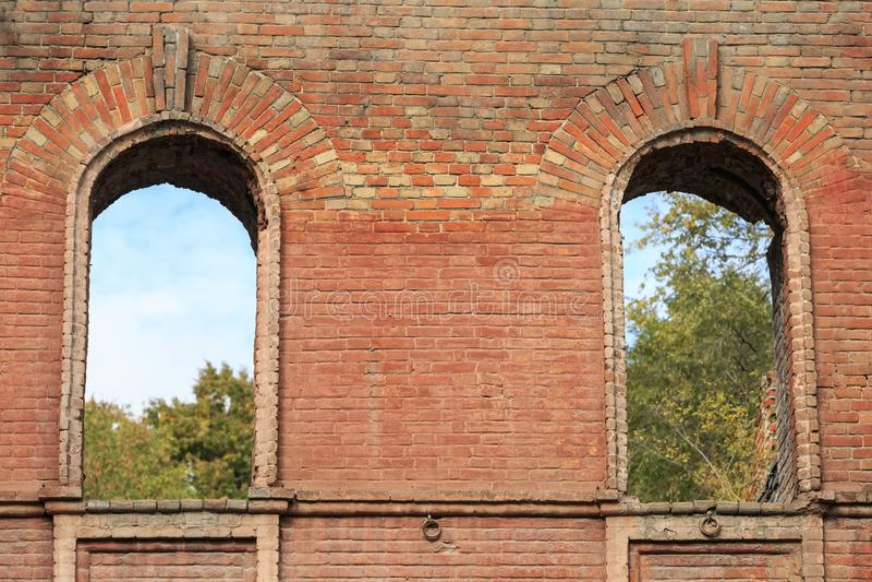 在一个古老房子的老砖墙的两通过窗口发射孔 免版税库存图片