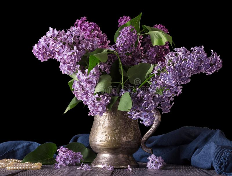 在一个古老花瓶的丁香,在蓝色织品和小珠旁边,在黑色 库存照片