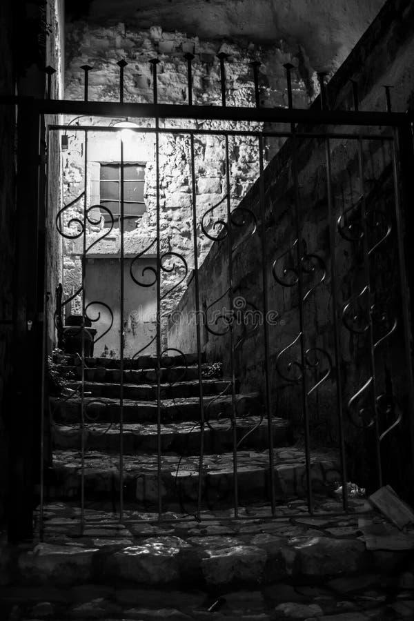 在一个古老钢门后的光照亮的石台阶 库存照片